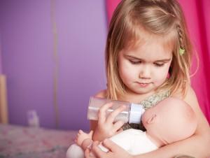Niña da de comer a muñeco bebé