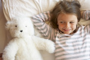 Young Girl Relaxing In Bed With Toy